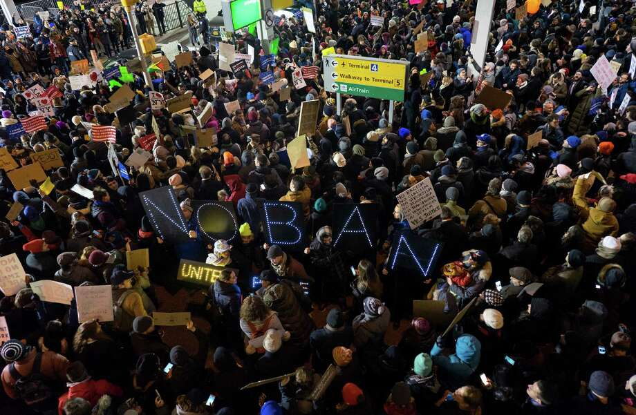 Protesters assemble at John F. Kennedy International Airport in New York, Saturday, Jan. 28, 2017, after earlier in the day two Iraqi refugees were detained while trying to enter the country. On Friday, Jan. 27, President Donald Trump signed an executive order suspending all immigration from countries with terrorism concerns for 90 days. Countries included in the ban are Iraq, Syria, Iran, Sudan, Libya, Somalia and Yemen, which are all Muslim-majority nations. Photo: Craig Ruttle, AP / FR61802 AP