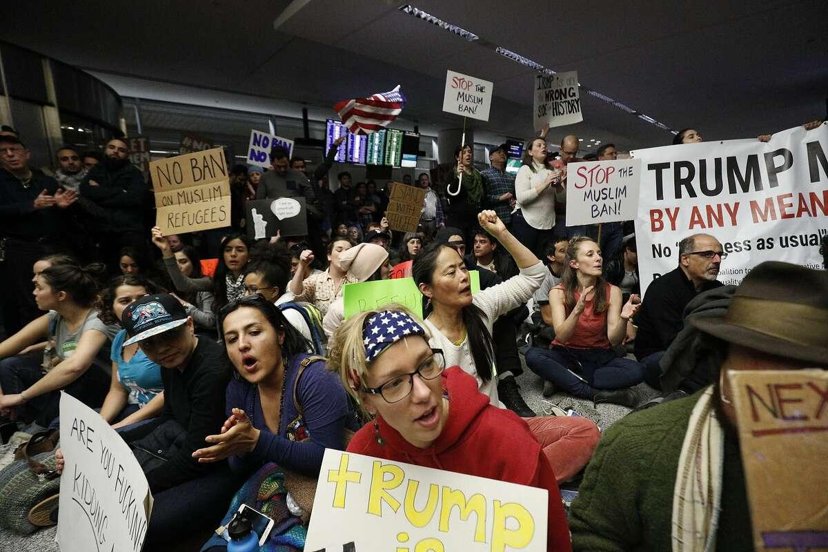 Karen Lopez, Kristy Magnuson, Nora Akino sit down at airport . Protestors block arrival lower deck roadway on Saturday, Jan. 28, 2017 in San Francisco, Calif.