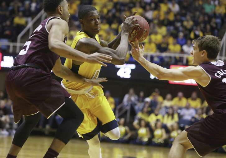 West Virginia guard Teyvon Myers (0) splits Texas A&M guard JC Hampton (5) and Texas A&M guard Chris Collins (12) as he drives to the basket during the second half of an NCAA college basketball game, Saturday, Jan. 28, 2017, in Morgantown, W.Va. (AP Photo/Raymond Thompson)
