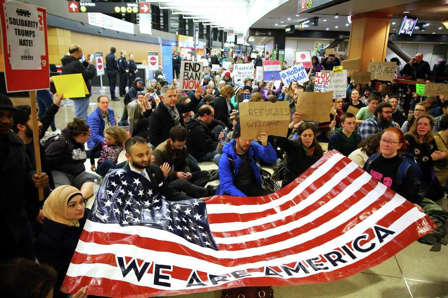 """Demonstrators sit down in the concourse and hold a sign that reads """"We are America."""" More than 1,000 people gather at Seattle-Tacoma International Airport, Saturday, January 28 to protest President Trump's immigration ban.  President Trump signed an executive order Friday that bars citizens from Iraq, Syria, Iran, Libya, Somalia, Sudan and Yemen from entering the U.S. for the next 90 days and suspends the admission of all refugees for 120 days. Photo: GENNA MARTIN, SEATTLEPI.COM / GENNA MARTIN, SEATTLEPI.COM"""