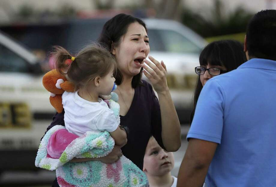 A woman holds her child after San Antonio police helped her and other shoppers exit the Rolling Oaks Mall, Sunday, Jan. 22, 2017, in San Antonio, after a deadly shooting. Retail analysts say malls and shopping centers aren't impacted in the long-term by violent events. Photo: Eric Gay /Associated Press / Copyright 2017 The Associated Press. All rights reserved.