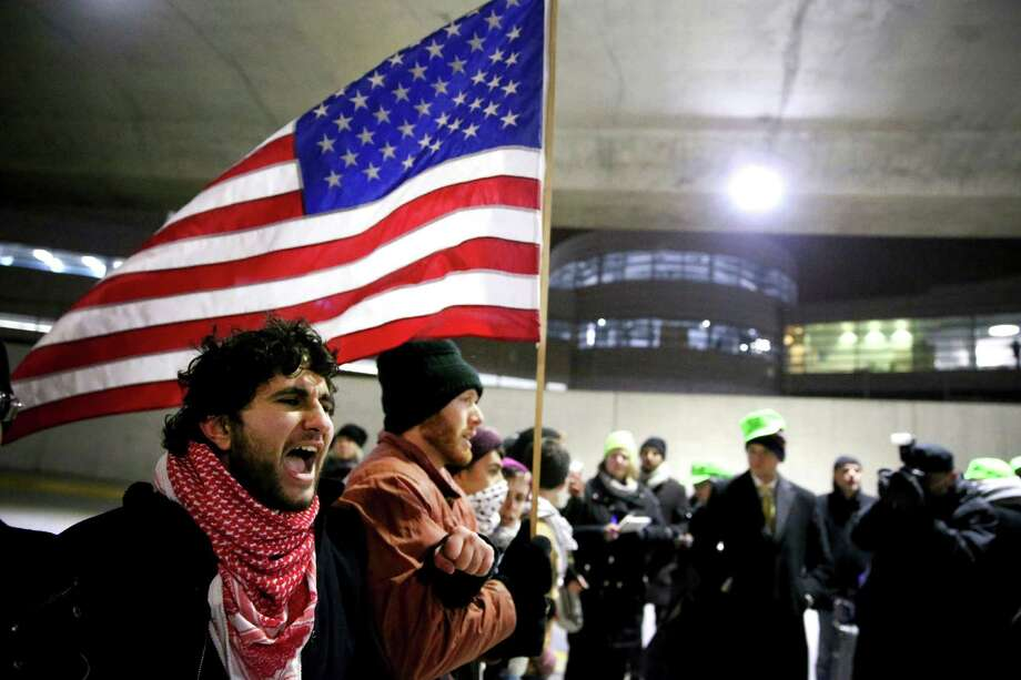 Protesters gather at O'Hare International Airport after people were detained, including green card holders, Saturday, Jan. 28, 2017, in Chicago. They were detained following President Donald Trump's executive order on Friday that bans legal U.S. residents and visa-holders from seven Muslim-majority nations from entering the U.S. for 90 days and puts an indefinite hold on a program resettling Syrian refugees. (Chris Sweda/Chicago Tribune via AP) Photo: Chris Sweda, AP / Chris Sweda/Chicago Tribune
