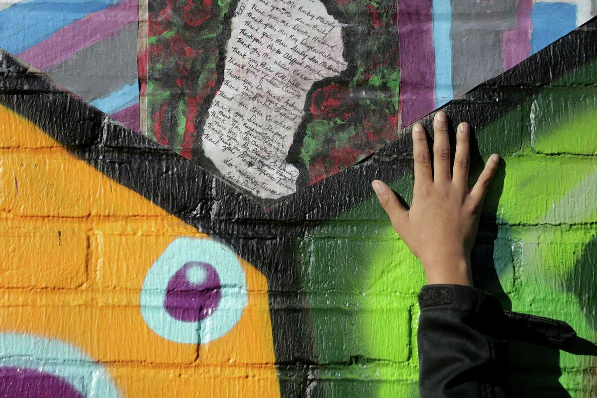 Students point to their contributions on the Beulah Shepard - Acres Homes Library mural on Saturday, Jan. 28, 2017, in Houston.