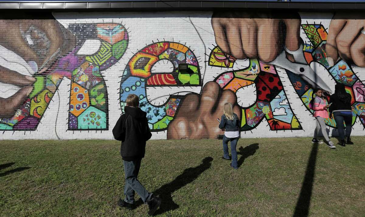Students who worked on a quilt-inspired mural on the side of the Beulah Shepard - Acres Homes Library get a closer look before the dedication on Saturday, Jan. 28, 2017, in Houston.