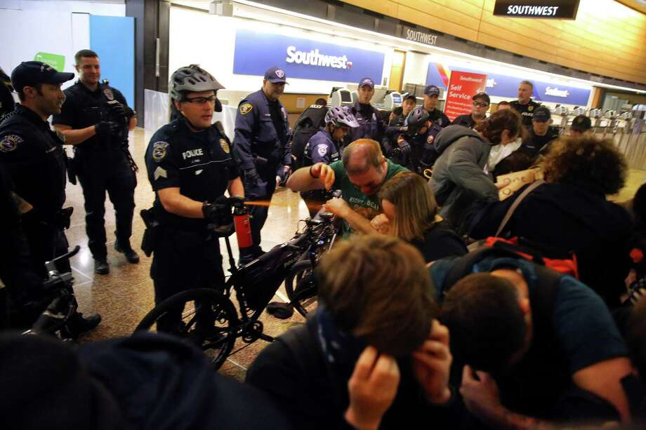 CORRECTION: An earlier version of this cutline misidentified the department of the police officer pictured.A Port of Seattle police officer uses pepper spray and push the last group of protesters out of the airport terminal after giving a final dispersal order around 2:00 a.m Sunday.More than 1,000 people gather at Seattle-Tacoma International Airport, Saturday, January 28 to protest President Trump's immigration ban.  President Trump signed an executive order Friday that bars citizens from Iraq, Syria, Iran, Libya, Somalia, Sudan and Yemen from entering the U.S. for the next 90 days and suspends the admission of all refugees for 120 days. Photo: SEATTLEPI.COM / GENNA MARTIN, SEATTLEPI.COM