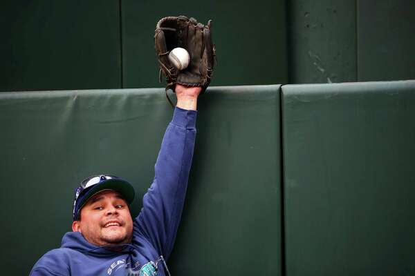 Aaron Youckton, of Yelm, pretends to make an outfield catch during Mariners FanFest at Safeco Field, Saturday, Jan. 28, 2017.