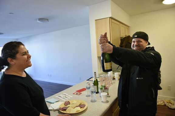 Jennifer Longaway watches as her husband Alec Longaway pops open a bottle of champagne in the kitchen of their new condo following a Habitat Terrace Home Dedication ceremony held by Habitat for Humanity of Greater San Francisco where they and 10 other families receive the keys to their new homes, in San Francisco, CA on Saturday, January 28, 2017.