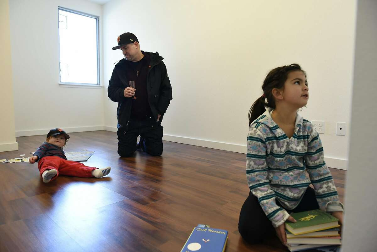 Alec Longaway plays with his son Keegan, 2, and daughter Grace, 7, in an empty upstairs bedroom of their new condo following a Habitat Terrace Home Dedication ceremony held by Habitat for Humanity of Greater San Francisco where they and 10 other families receive the keys to their new homes, in San Francisco, CA on Saturday, January 28, 2017.