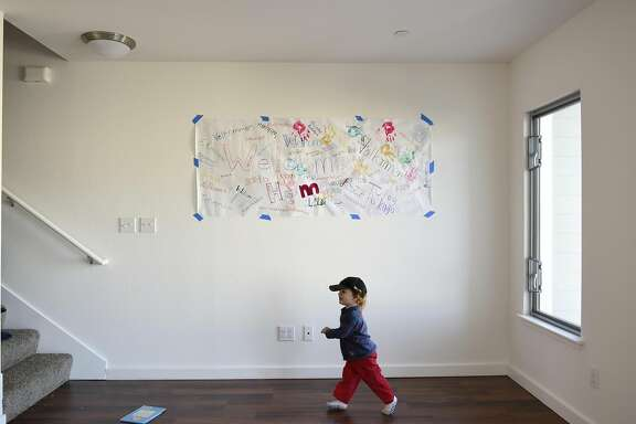 Keegan Longaway, 2, runs past a welcome banner, in his family's new condo, following a Habitat Terrace Home Dedication ceremony held by Habitat for Humanity of Greater San Francisco where they and 10 other families receive the keys to their new homes, in San Francisco, CA on Saturday, January 28, 2017.