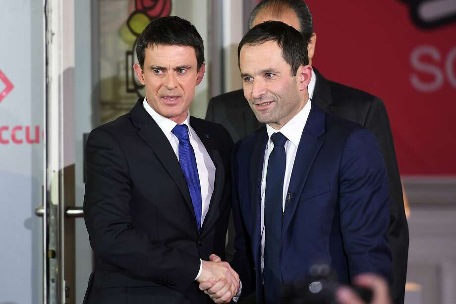 Benoit Hamon (right), winner of the Socialist Party presidential nomination, shakes hands with defeated candidate Manuel Valls at party offices in Paris. Photo: ERIC FEFERBERG, AFP/Getty Images
