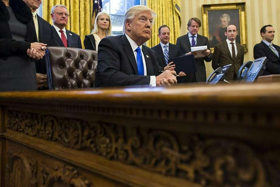 FILE -- President Donald Trump surrounded by senior staff while signing executive orders in the Oval Office, on Capitol Hill in Washington, Jan. 28, 2017. An executive order President Donald Trump signed on Jan. 27, 2017 gives preference to refugees who belong to a religious minority that has been persecuted, but a broad array of clergy, including evangelical and mainline Protestant leaders, has strongly denounced the order as discriminatory, misguided and inhumane. (Al Drago/The New York Times) Photo: AL DRAGO, NYT