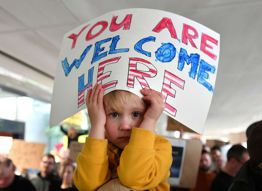 Hattie Burke-foreuic holds up a sign on her father's shoulders during a protest at San Francisco International Airport January 29, 2017. U.S. President Donald Trump issued an executive order yesterday barring citizens of seven Muslim-majority countries from entering the United States for the next 90 days and suspends the admission of all refugees for 120 days. Photo: JOSH EDELSON, AFP/Getty Images