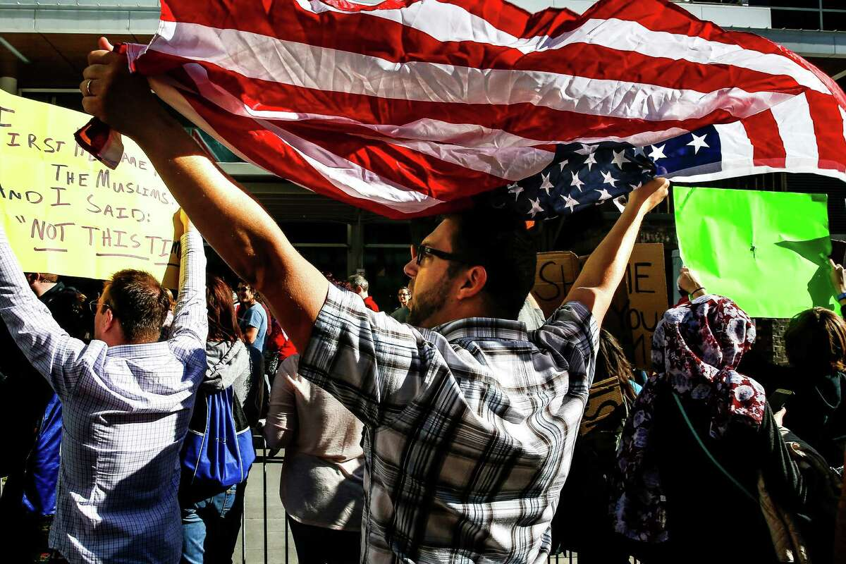People protest Donald Trump's immigration orders outside Super Bowl Live Sunday, Jan. 29, 2017 in Houston.