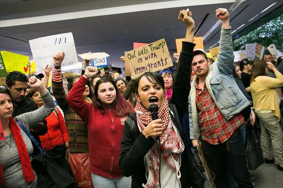 Lara Kiswani leads the crowds in a chat during the second day of demonstrations at arrivals terminal at the San Francisco Airport in San Francisco, Calif., for a demonstration against Donald Trump's executive order that bars citizen of seven from predominately Muslim countries from entering the U.S., Sunday, January 29, 2017.