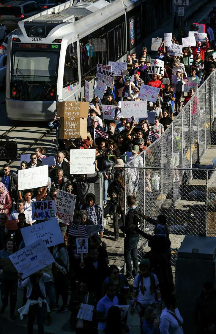 Hundreds of people protesting President Donald Trump's executive order on immigration march down Rusk Street outside Super Bowl Live in downtown Houston Sunday. ( Michael Ciaglo / Houston Chronicle )