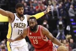 Houston Rockets guard James Harden, right, dribbles around Indiana Pacers forward Paul George in the first half of an NBA basketball game, Sunday, Jan. 29, 2017, in Indianapolis. (AP Photo/R Brent Smith)