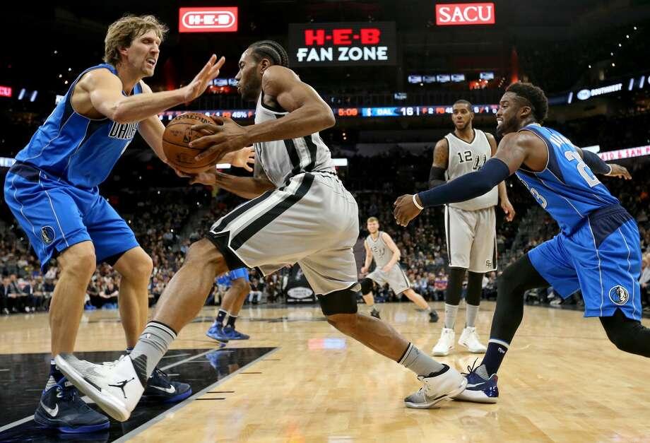 San Antonio Spurs' Kawhi Leonard looks for room between Dallas Mavericks' Dirk Nowitzki (left) and Wesley Matthews during first half action Sunday Jan. 29, 2017 at the AT&T Center. Photo: Edward A. Ornelas/San Antonio Express-News
