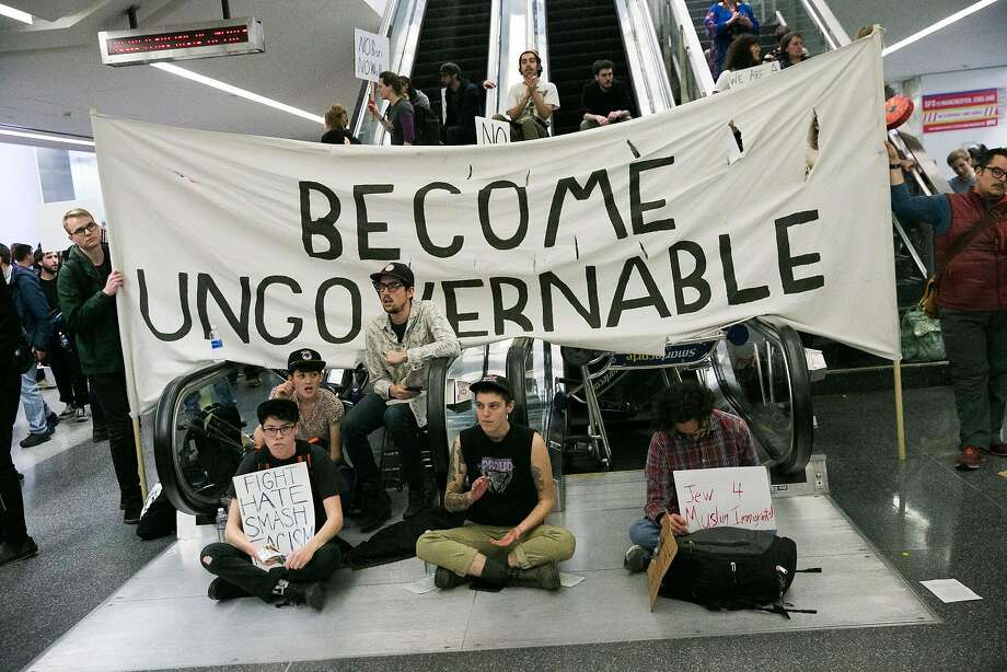 Demonstrators block escalators at the departures terminal at the San Francisco Airport in San Francisco, Calif., for a demonstration against Donald Trump's executive order that bars citizen of seven from predominately Muslim countries from entering the U.S., Sunday, January 29, 2017. Photo: Mason Trinca, Special To The Chronicle