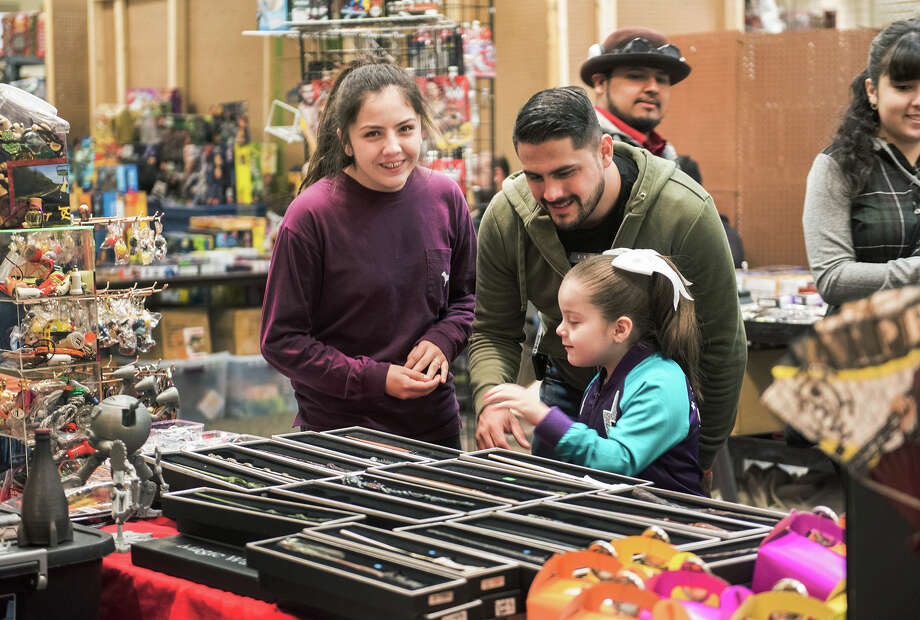 Ashley Hinojosa smiles at the camera as Ielly Hinojosa and Eddie Hinojosa browse through a selection of Harry Potter wands on Sunday, January 29, 2017 during the South Texas Collectors Expo at the Texas A&M International University Student Center. Photo: Danny Zaragoza/Danny Zaragoza | Laredo Morning