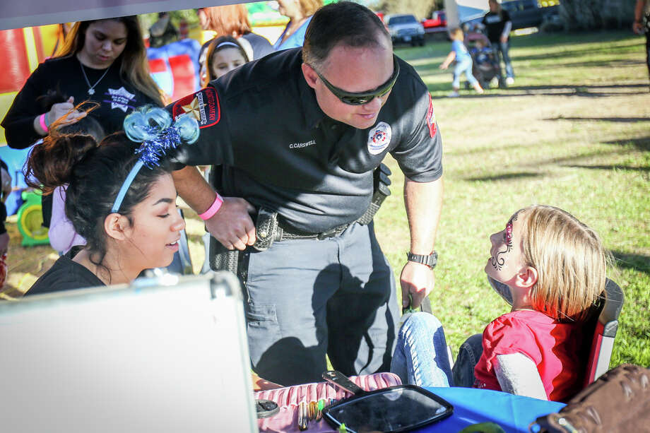 Montgomery police officer Chris Carswell chats with his daughter Willow, 6, after she gets a face painting during the Americans Stand United for the Men and Women in Blue event on Sunday in downtown Montgomery. Photo: Michael Minasi, Staff Photographer / © 2017 Houston Chronicle