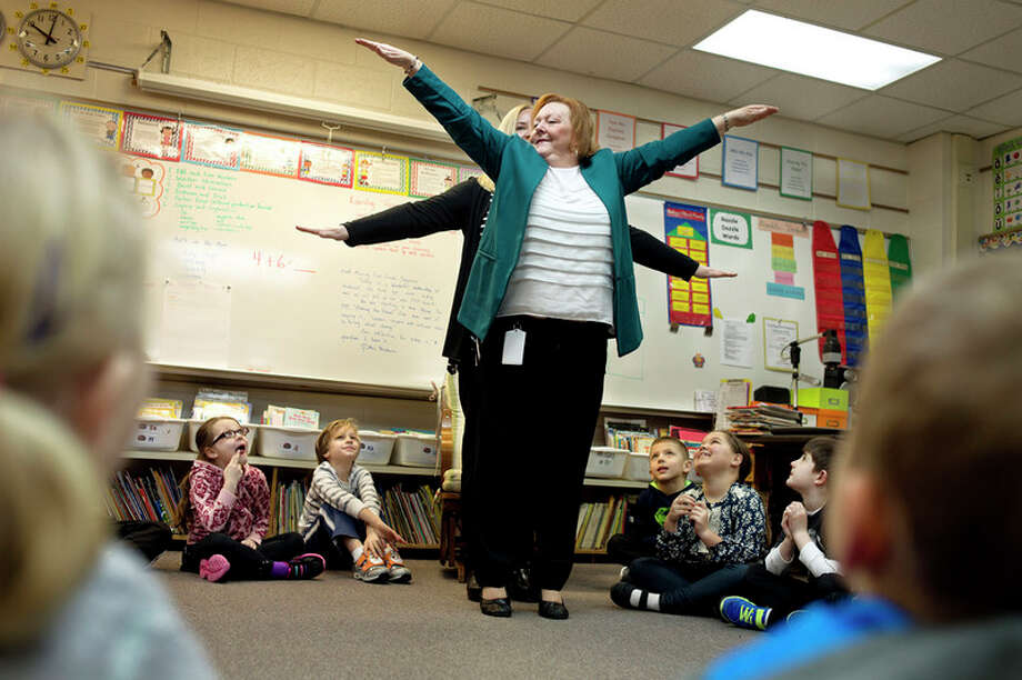 BRITTNEY LOHMILLER | blohmiller@mdn.net Woodcrest Elementary first grade teacher Lynn Verdusco and parent volunteer Jennifer Edmonds demonstrate to the class how to use their bodies to visual demonstrate the math sentence 4+6=10 Wednesday morning. / Midland Daily News