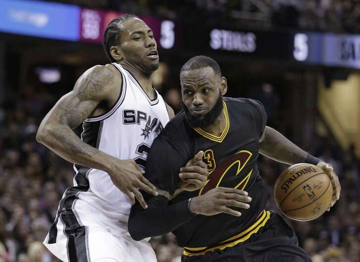 Cavaliers' LeBron James drives against the Spurs' Kawhi Leonard during the second half on Jan. 21, 2017, in Cleveland.