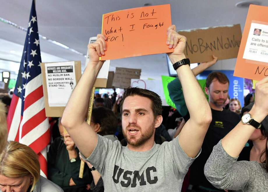 Iraq war veteran Evan Cohen holds up a sign during a protest at San Francisco International Airport in San Francisco, California on January 29, 2017. U.S. President Donald Trump issued an executive order yesterday barring citizens of seven Muslim-majority countries from entering the United States for the next 90 days and suspends the admission of all refugees for 120 days. / AFP PHOTO / Josh EdelsonJOSH EDELSON/AFP/Getty Images Photo: JOSH EDELSON, Stringer / AFP/Getty Images / AFP or licensors