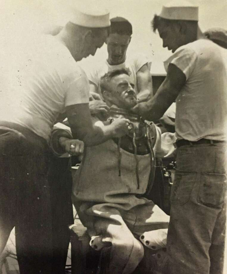 This circa 1943 photo provided by the Hartle family shows Navy diver Ken Hartle getting into his dive suit in Pearl Harbor, Hawaii. Hartle, believed to be the oldest surviving salvage diver who worked the wreckage left after the Japanese attack on Pearl Harbor in World War II, died Tuesday, Jan. 24, 2017. He was 103. (Courtesy Hartle Family via AP) Photo: Anonymous, HONS / Associated Press / Hartle Family
