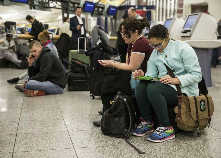 Delta passengers sit down while waiting in line at Hartsfield-Jackson International Airport after Delta Air Lines grounded all domestic flights due to automation issues Sunday. On Monday, 110 flights had been canceled and the airline said more may follow. However, it said the issue had been resolved. Photo: Branden Camp /Associated Press / FR171034 AP