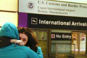 An Iranian woman, left, embraces her crying friend who emerges three hours after her plane arrived from Iran to Logan Airport in Boston on Jan. 29, 2017. People waited at Logan for international arrivals from countries where immigration was restricted by President Trump's executive order.