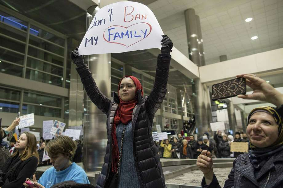 Demonstrators hold signs and chant in the baggage claim area during a protest against President Donald Trump's executive order banning travel to the United States by citizens of several countries Sunday at Detroit Metropolitan Airport. Automakers are walking a tightrope as they court Trump, whose policies on clean-air standards, corporate taxes and trade will affect their fortunes. They have to balance that against other considerations closer to home: The traditional three U.S. automakers are based in Michigan, which backed Trump's surprise victory but also has a substantial Middle Eastern population troubled by his executive order on immigration. Photo: Jeffrey M. Smith /Associated Press / Copyright 2017 The Associated Press. All rights reserved.