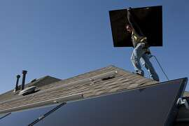 A worker with a solar installation company prepared to install a rooftop system.