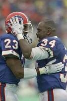 Buffalo's Kenneth Davis (23) and Thurman Thomas (34) celebrate after Davis touchdown in the second quarter of AFC Championship game in Orchard Park, NY., Sunday, Jan. 21, 1991, with the Los Angeles Raiders. The Bills advance to next Sunday's Super Bowl with a 51-3 victory over the Raiders. (AP Photo/Mike Groll)