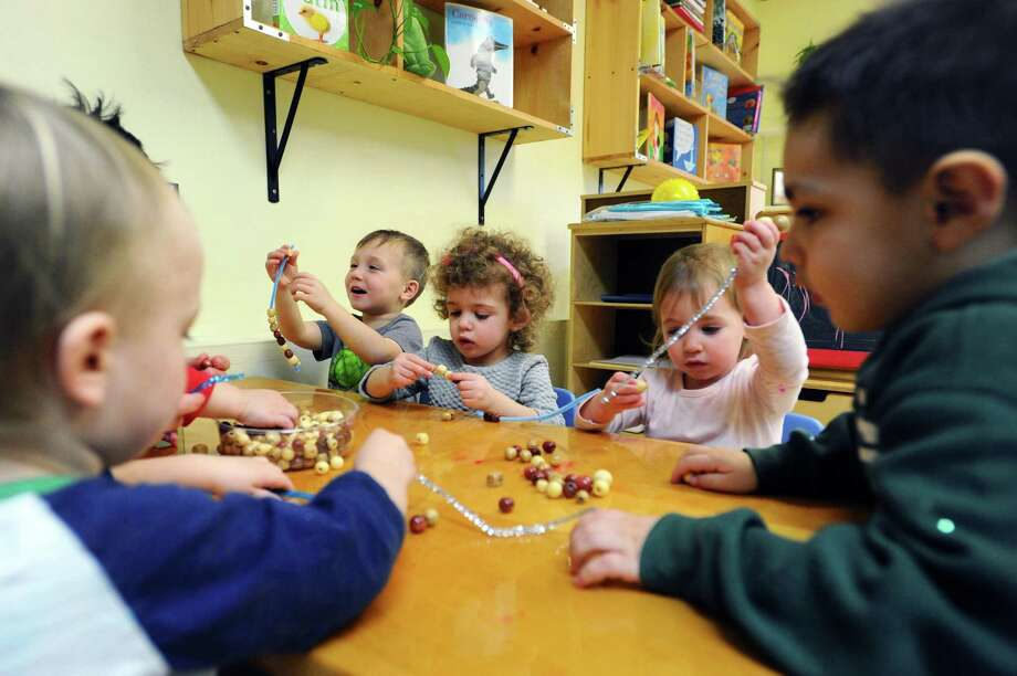 From center left, Otis, 3, Charlie, 2, and Aria, 2, make bead necklaces inside the new play-based Sound Beach Day School on Fairfield Ave. in Stamford, Conn. on Thursday, Jan. 26, 2017. Photo: Michael Cummo / Hearst Connecticut Media / Stamford Advocate