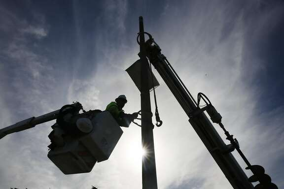Chris Lopez, PUC electrical line helper,  secures a cinch around a light pole while working with others to remove it from Point Lobos Avenue  on Monday, January 30, 2017 in San Francisco, Calif.