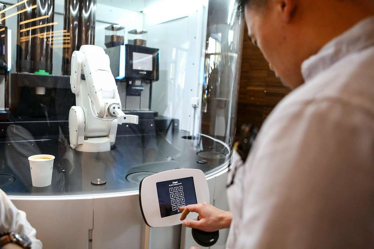 A customer who did not wish to be identified enters a pin number to receive his drink from the new robotic arm at Cafe X, the first robotic cafe, located within the Metreon in San Francisco, Calif. on Monday, January 30, 2017.