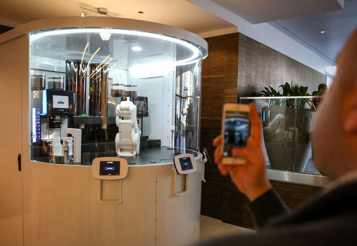 Emil Michael takes photos of the robotic arm at Cafe X, the first robotic cafe, located within the Metreon in San Francisco, Calif. on Monday, January 30, 2017.