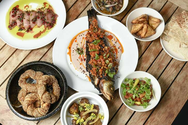 """A center piece of whole fish wrapped in olive leaves and baked surrounded by a variety of mezzas, served during husband and wife chefs Laura and Sayat Oxyilmaz's pop-up restaurant """"Istanbul Modern"""" in San Francisco, CA on Sunday, January 29, 2017."""