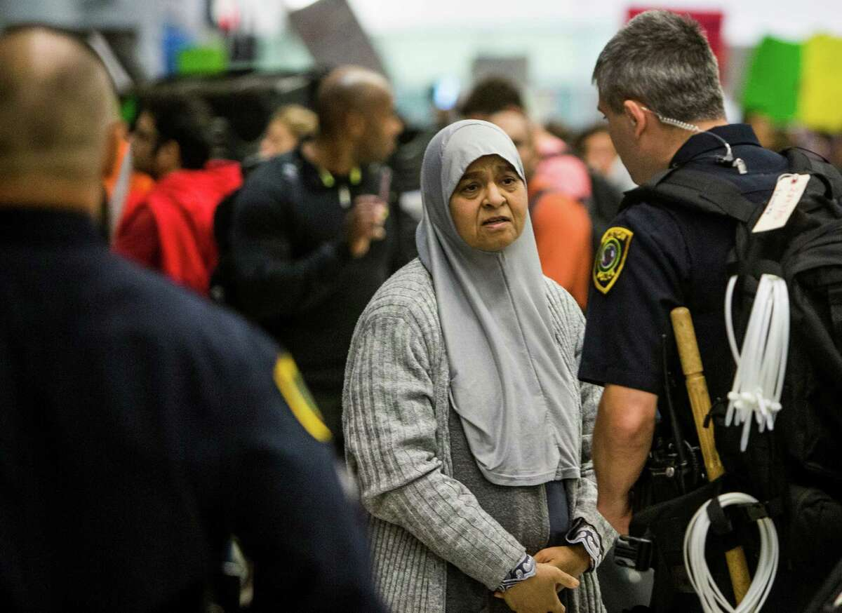 A woman talks to a police officer during a protest against President Donald Trump's executive orders on immigration at George Bush Intercontinental Airport on Sunday, Jan. 29, 2017, in Houston. ( Brett Coomer / Houston Chronicle )