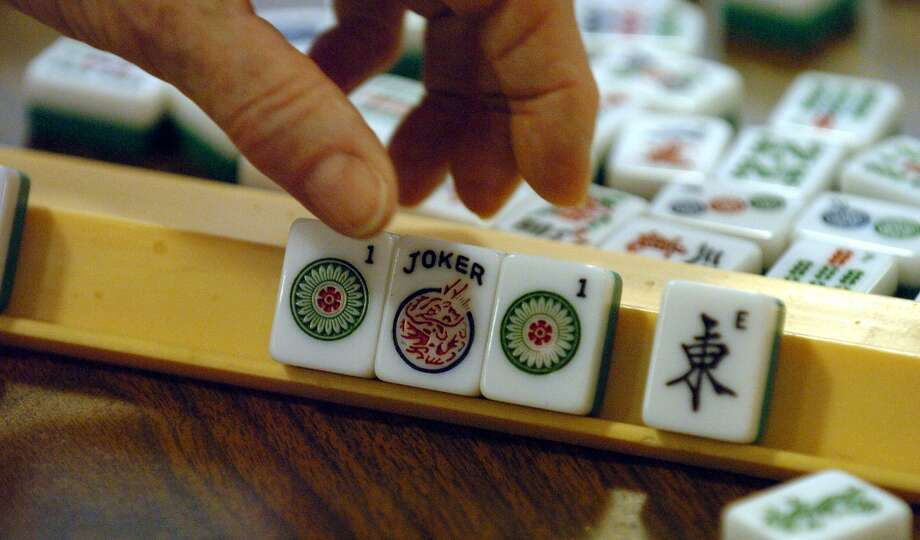 Mah Jong is an ancient Chinese game played with domini-like tiles and players aim to acquire a winning hand. This file photo is from a regular weekly game at the Lion's Field Adult Center on Broadway in 2004. JOHN DAVENPORT / STAFF Photo: JOHN DAVENPORT /SAN ANTONIO EXPRESS-NEWS / SAN ANTONIO EXPRESS-NEWS