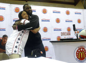 Legacy Christian Academy's Alexis Morris gets a big hug of congratulations from coach Yannick Denson during a ceremony in which she was honored and presented with her McDonald's All-American game jersey and hat after school Monday. Morris, who will be playing basketball for Baylor in the fall, was one of 12 girls chosen to be part of the West Team, which faces the all-star team from the East March 29 at Chicago's United Center. She is also the first player to make the McDonald's roster since Ozen's Kendrick Perkins played for the boys' all-star team in 2003. Photo taken Monday, January 30, 2017 Kim Brent/The Enterprise