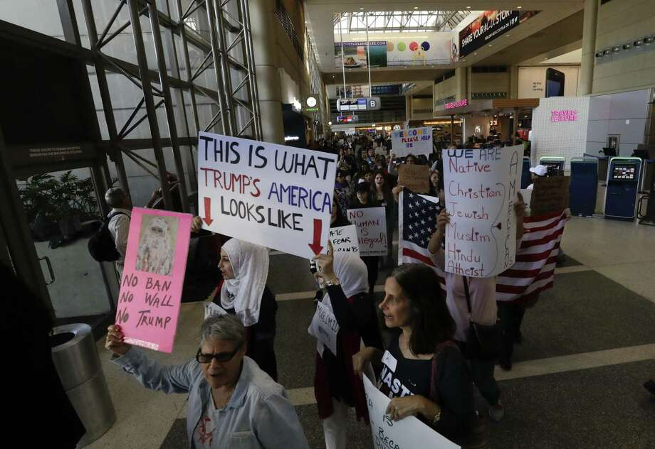 Demonstrators march inside Tom Bradley International Terminal during a protest by airport service workers from United Service Workers West union Monday, Jan. 30, 2017, at Los Angeles International Airport. The vigil in support of travelers affected by the executive order restricting travel from seven primarily Muslim countries. (AP Photo/Chris Carlson) Photo: Chris Carlson, STF / Associated Press / Copyright 2017 The Associated Press. All rights reserved.