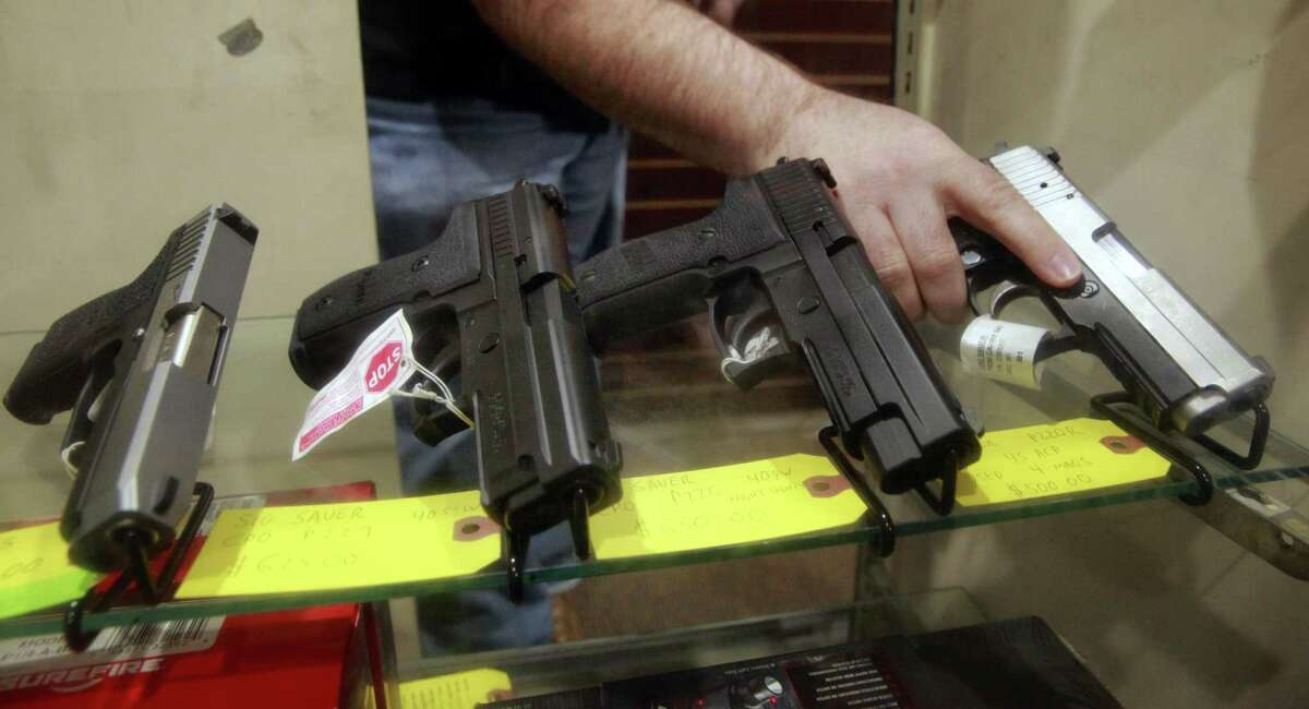 Todd Settergren of Setterarms gun shop, handles pistols inside his display case on Friday Jan. 13, 2017, in Walnut Creek, Ca. Settergren says California gun laws have gone too far and he welcomes the chance that the federal government under the Trump administration will ease restrictions on concealed carry permits and specific weapon bans.