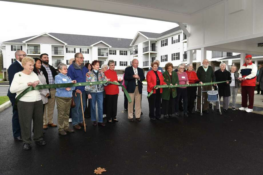 Town of Wilton Supervisor Art Johnson, center, is surrounded by residents and family members as he cuts the ribbon during the grand opening of The Summit at Saratoga on Thursday, Dec. 1, 2016 in Saratoga Springs, N.Y. The Summit at Saratoga is a 110-unit senior independent living community for those 55 and older. (Lori Van Buren / Times Union) Photo: Lori Van Buren / 20039015A