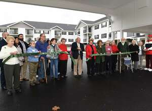 Town of Wilton Supervisor Art Johnson, center, is surrounded by residents and family members as he cuts the ribbon during the grand opening of The Summit at Saratoga on Thursday, Dec. 1, 2016 in Saratoga Springs, N.Y. The Summit at Saratoga is a 110-unit senior independent living community for those 55 and older. (Lori Van Buren / Times Union)
