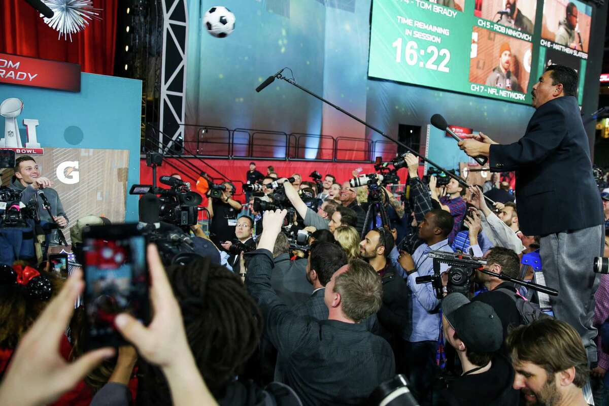 New England Patriots quarterback Tom Brady (12) passes a soccer ball back to Guillermo Rodriguez from Jimmy Kimmel Live after signing it during Super Bowl LI Opening Night at Minute Maid Park Monday, Jan. 30, 2017 in Houston.