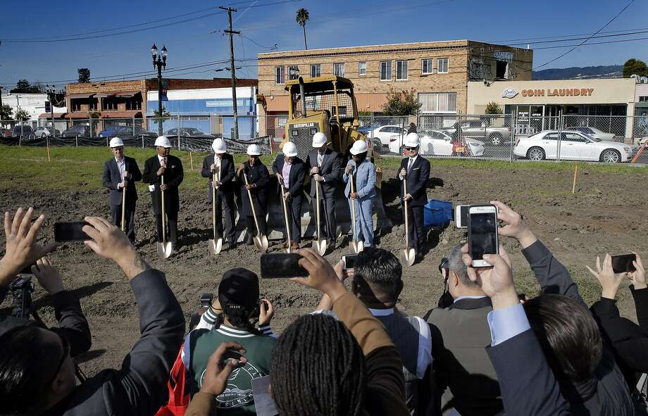 Top: Area residents take photos during a groundbreaking ceremony for the new development in Oakland's Seminary neighborhood. Above: Jose Corona of the mayor's office speaks during the event Monday. Photo: Carlos Avila Gonzalez, The Chronicle