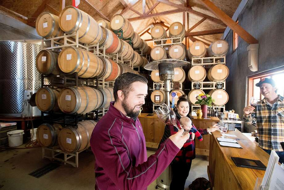 Maclain Atkinson tastes wine at Amador Cellars in Plymouth. At right is winemaker Michael Long. Photo: Noah Berger, Special To The Chronicle
