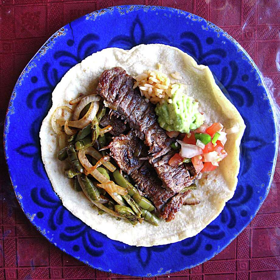 A carne asada taco on a handmade flour tortilla from Taquería Potrillo. Built from a plate that includes grilled nopales, grilled onions, pico, rice beans and guacamole. Photo: Mike Sutter /San Antonio Express-News