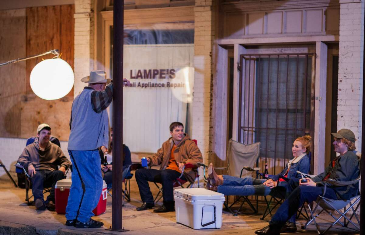 """Actor Barry Corbin, standing, and other cast members take a break during the filming of """"Windsor."""""""
